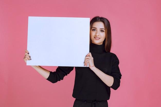 正方形のアイデアボードを保持している黒いセーターの女性。