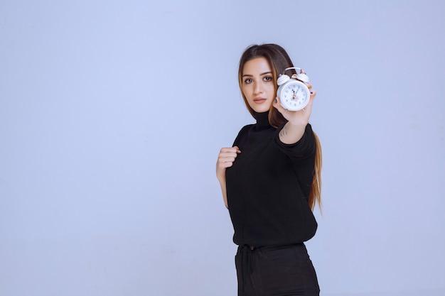 알람 시계를 들고 그것을 홍보하는 검은 스웨터에 여자.