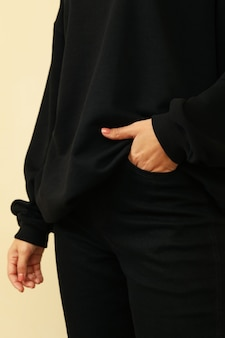 Женщина в черном свитере держит руку в кармане черных джинсов