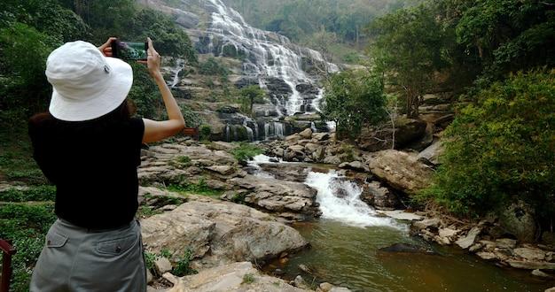 Женщина в черной футболке фотографировать красивый водопад на смартфон.