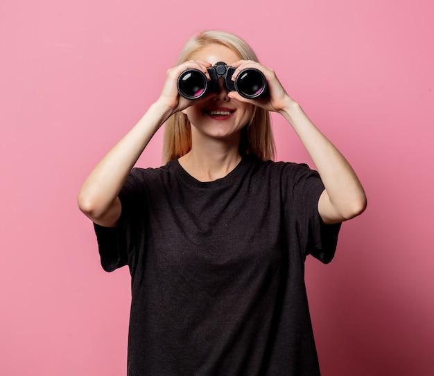 Женщина в черной футболке с биноклем на розовом