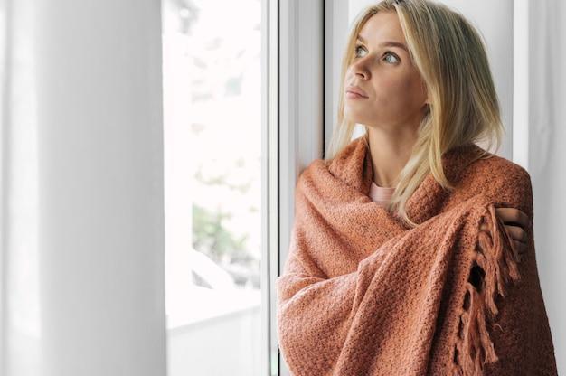Женщина в одеяле дома во время пандемии сидит рядом с окном