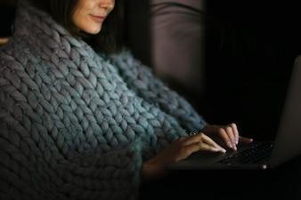 Woman in blanket browsing laptop in dark room