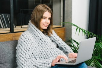 Woman in blanket using laptop