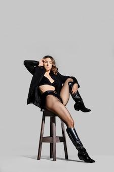블레이저와 가죽 부츠를 입은 여성이 스튜디오의 의자에 앉아 다리를 앞으로 뻗습니다.