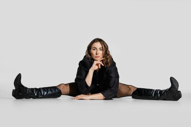 블레이저와 가죽 부츠를 입은 여성이 스튜디오 바닥에 앉아 다리를 쭉 뻗습니다.