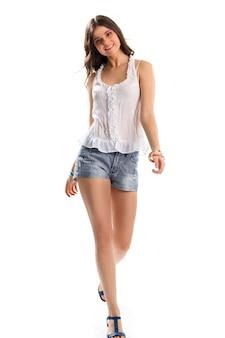 블라우스를 입은 여자가 걷고 있습니다. 짧은 반바지에 웃는 소녀. 새로운 면 블라우스와 팔찌. 심플한 여성복.