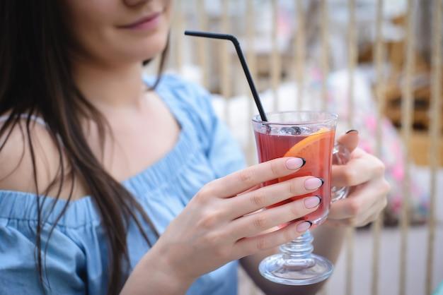 おいしいグリューワインを飲む青いブラウスの女性