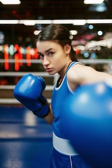 青いボクシンググローブの女性がヒット、リングのボックストレーニング。ジムでの女性のボクサー、スポーツクラブでのキックボクシングのスパーリング、女の子のキックボクサーのトレーニング