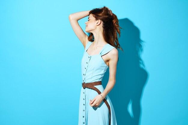 孤立した背景のポーズの青いドレスグラマー笑顔の女性。高品質の写真
