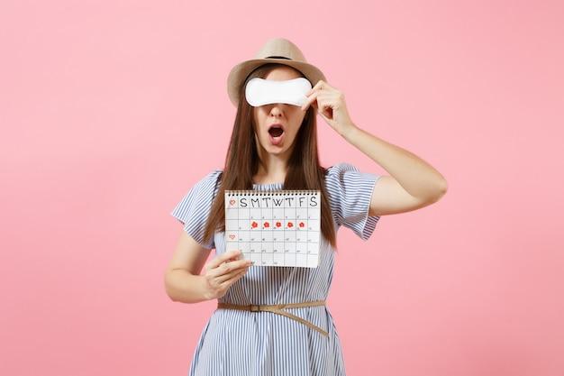 파란 드레스를 입은 여성, 생리대를 들고 있는 모자, 눈을 가리고, 분홍색 배경에 격리된 월경일을 확인하기 위한 여성의 생리 달력. 의료, 건강 관리, 부인과 개념입니다. 복사 공간