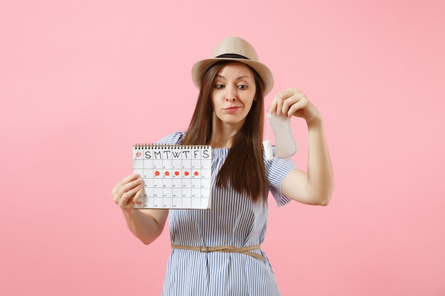 파란 드레스를 입은 여성, 생리대를 들고 있는 모자, 탐폰 여성 기간 달력, 분홍색 배경에 격리된 월경일을 확인합니다. 의료, 건강 관리, 부인과 선택 개념입니다. 공간을 복사합니다.