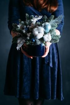 사슴, 목화, 가짜 눈 손수 전나무 트리 배열을 들고 파란 드레스에 여자.