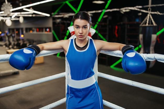 ボクシングのリングの隅に立っている青い手袋の女性、ボックストレーニング。ジムの女性ボクサー、スポーツクラブのキックボクシングスパーリング