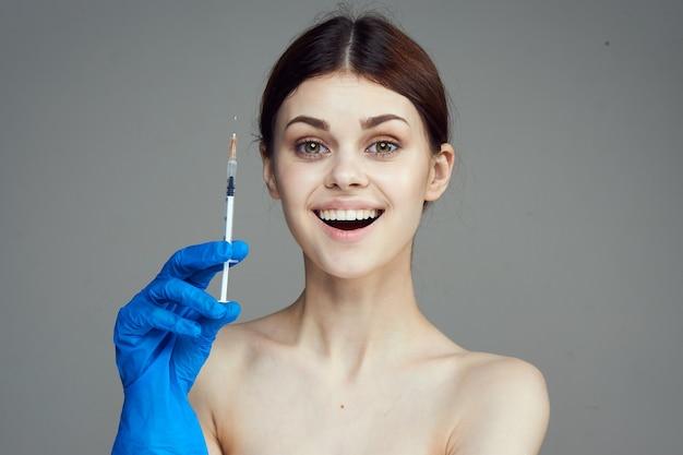 Женщина в синих перчатках со шприцем в руке с лечением инъекций ботокса против морщин. фото высокого качества