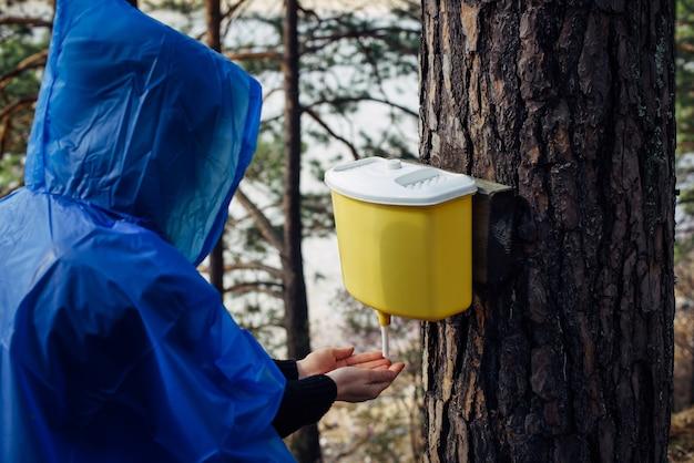 青いレインコートを着た女性は、木にぶら下がっている洗面台で手を洗います。雨上がりの朝、川沿いの森のツーリストキャンプで。フードに隠された少女の顔。ハイキングのライフスタイル。