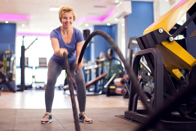 青いシャツを着た女性とジムでロープを使った短い髪のトレーニング。人、フィットネス、健康の概念
