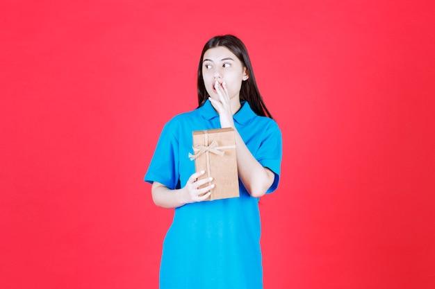 골 판지 미니 선물 상자를 들고 파란색 셔츠에 여자와 혼란 보인다.
