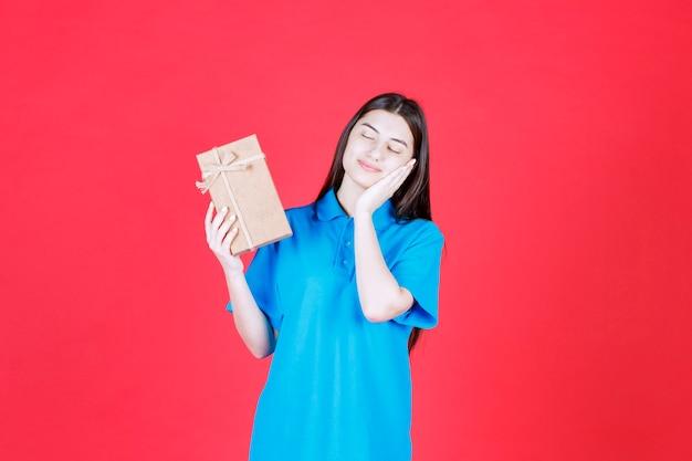 段ボールのミニギフトボックスを保持し、眠くて疲れているように見える青いシャツの女性。