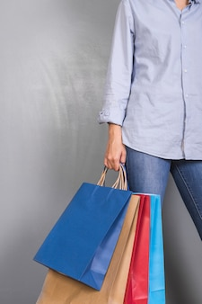 Woman in blue shirt holding shopping bags
