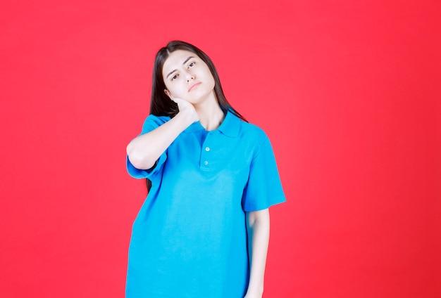 青いシャツを着た女性が立っていて、疲れて眠そうに見えます。