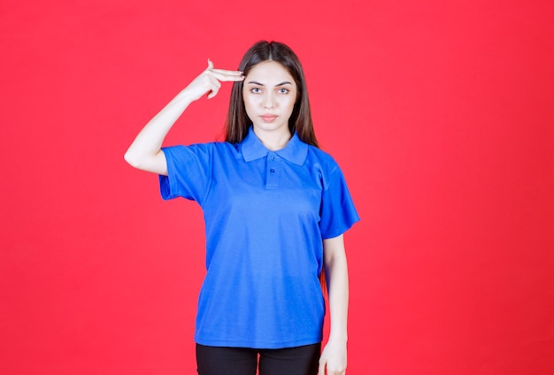 Женщина в синей рубашке стоит на красной стене и выглядит смущенной и задумчивой.