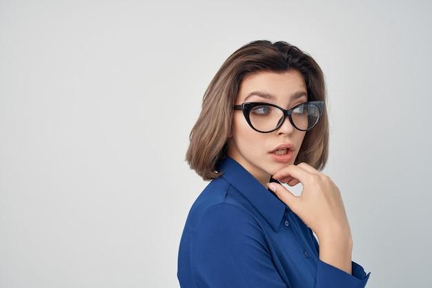 眼鏡をかけている青いシャツの女性は、エレガントなスタイルのビューをトリミングしました
