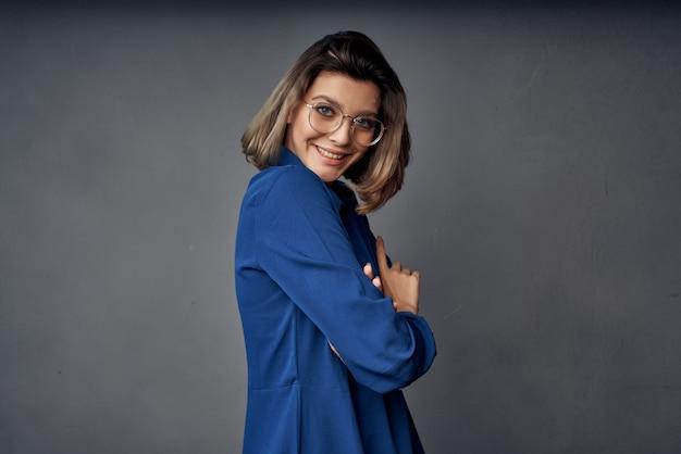 グラマーファッションを提起する眼鏡をかけている青いシャツの女性