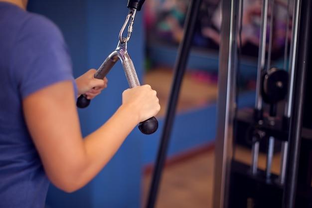 ジムで短い髪のトレーニング腕を持つ青いシャツの女性。人、フィットネス、健康の概念