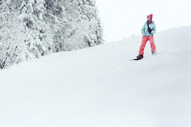 青いスキージャケットとピンクのズボンを着た女性が、スノーボードの雪が降った丘の下を行く