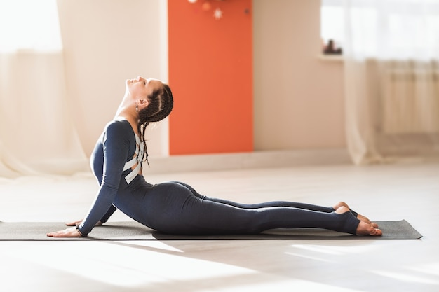 ヨガを練習している青いスポーツウェアの女性は、ブジャンガサナ運動コブラポーズを実行します