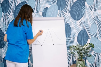 Woman in blue t-shirt drawing graph with marker on flipchart against wallpaper