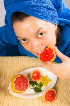 青いタオルを着た女性はグレープフルーツを食べ、スキンケアに使用します。