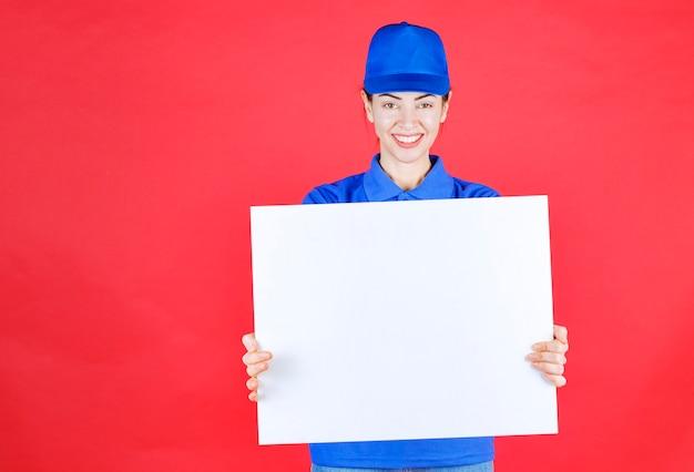 Женщина в синей форме и берете держит информационный стол белого квадрата и чувствует себя позитивно.