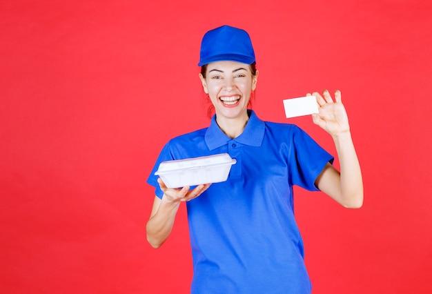 Женщина в синей форме держит белую пластиковую коробку для еды на вынос для доставки и представляет свою визитную карточку клиенту.