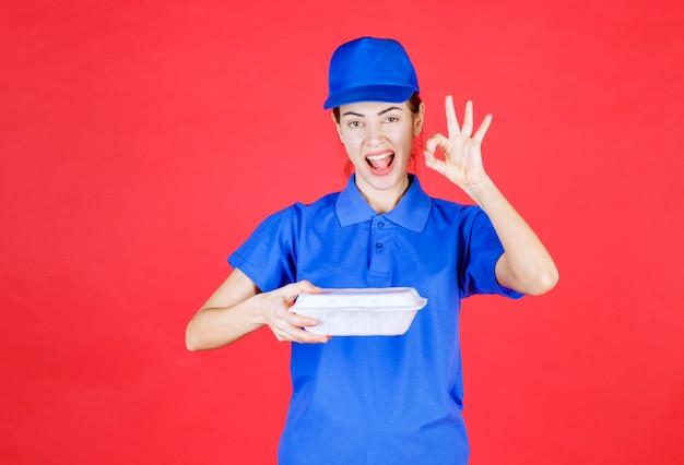 Женщина в синей форме держит белую пластиковую коробку на вынос для доставки и показывает знак удовлетворения.
