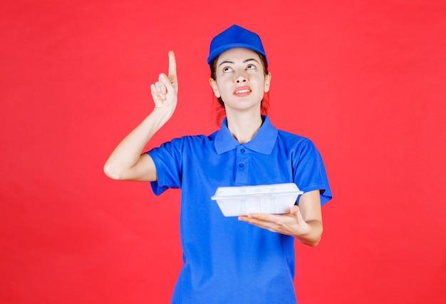Женщина в синей форме держит белую пластиковую коробку для еды на вынос для доставки и показывает что-то.