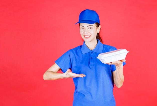 Женщина в синей форме держит белую пластиковую коробку на вынос для доставки.