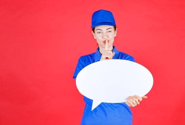 卵形のアイデアボードを保持し、沈黙を求めている青い制服を着た女性。