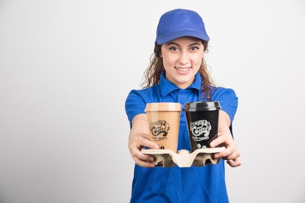 흰색 바탕에 커피 두 잔을 들고 파란색 제복을 입은 여자. 고품질 사진