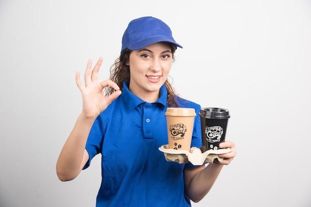 파란색 제복을 입은 여자는 흰색 바탕에 커피 두 잔으로 확인 제스처를 보여줍니다.