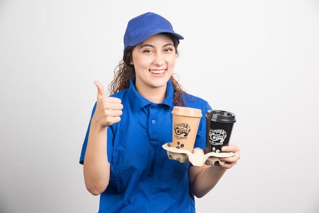 파란색 제복을 입은 여자는 흰색 바탕에 커피 두 잔과 함께 엄지 손가락을 보여줍니다. 고품질 사진