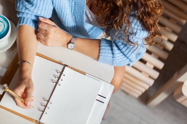 コーヒーショップの青い暖かいセーターを着て、青いラテのカップでクリスマスの買い物リストを書いている女性。クリスマス休暇の計画。コンセプトの整理と計画。