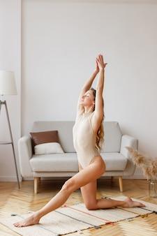 家の居間でヨガをしているボディースーツの女性