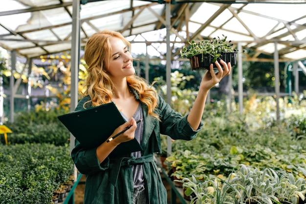 多種多様な生きている植物がたくさんある植物園の女性