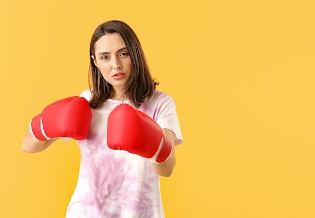 Женщина в боксерских перчатках на цветном фоне. концепция феминизма