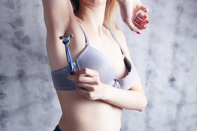 ブラジャーを着た女性がかみそりで脇の下を剃る