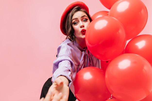 Женщина в ярком берете и фиолетовой блузке удивленно смотрит, тянется к камере и держит воздушные шары.