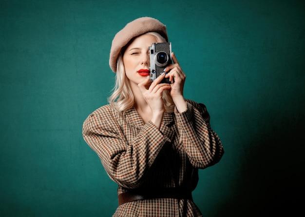녹색 벽에 빈티지 카메라와 함께 영국 스타일의 재킷과 베레모에 여자