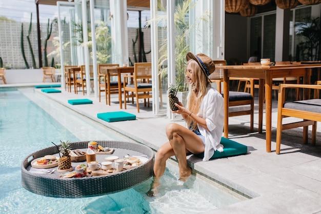 수영장 근처 휴식하는 동안 파인애플 칵테일을 마시는 갈색 모자에있는 여자. 주말 아침에 리조트 카페에서 차가운 웅장한 금발 여성 모델.